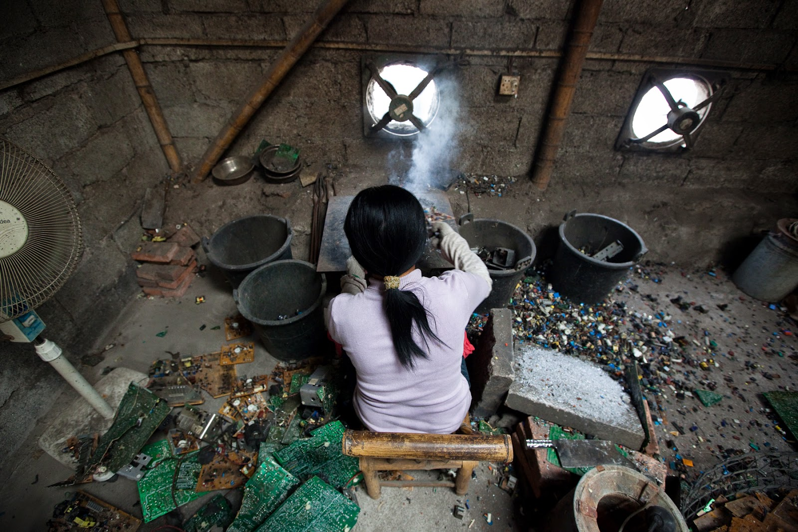 A 'Recycling Lab' from the Global South: Woman cooking circuit boards in a makeshift kitchen